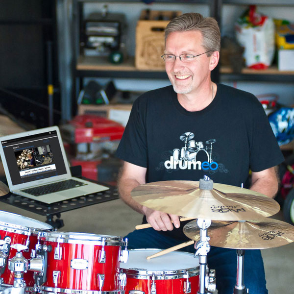 Man practicing drums with the Drumeo drum lesson platform